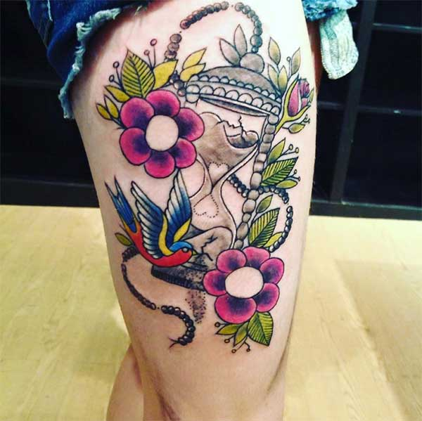 bird, flower and timer tattoo ink design on thigh