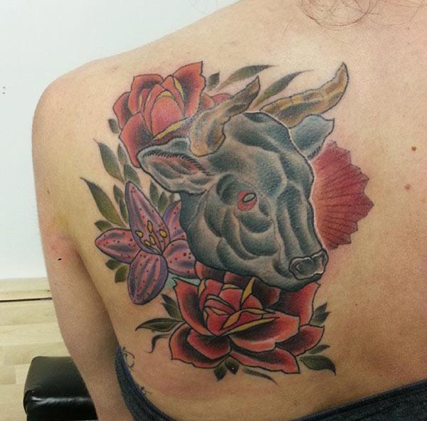 flowers blends wonderfully with Taurus tattoo on back of women