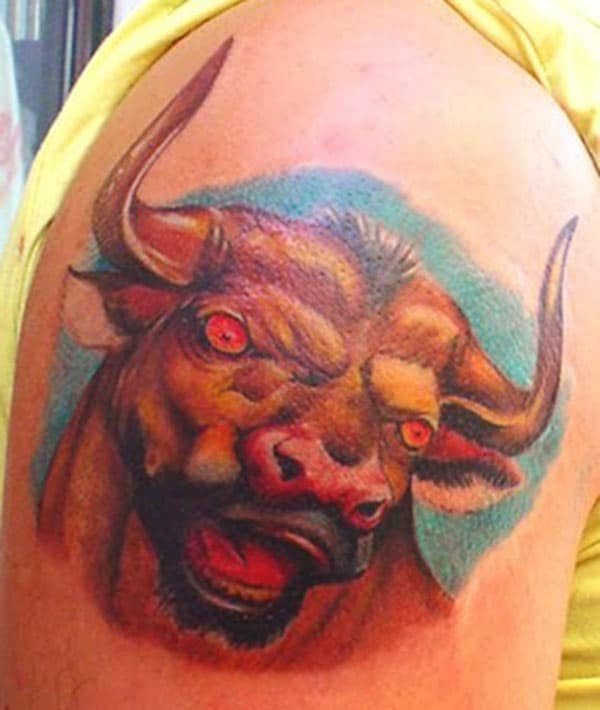 red and green mixes well in this Taurus tattoo on upper arm
