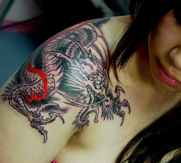 stunning colorful dragon tattoo on the woman's shoulder