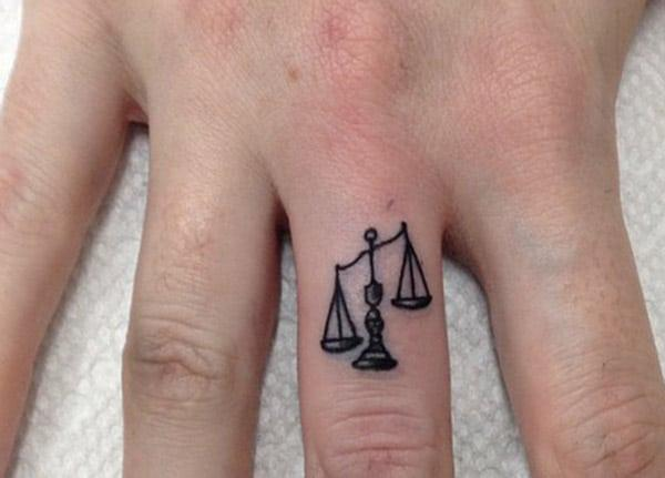 The Balance on the middle finger in this Libra tattoo design