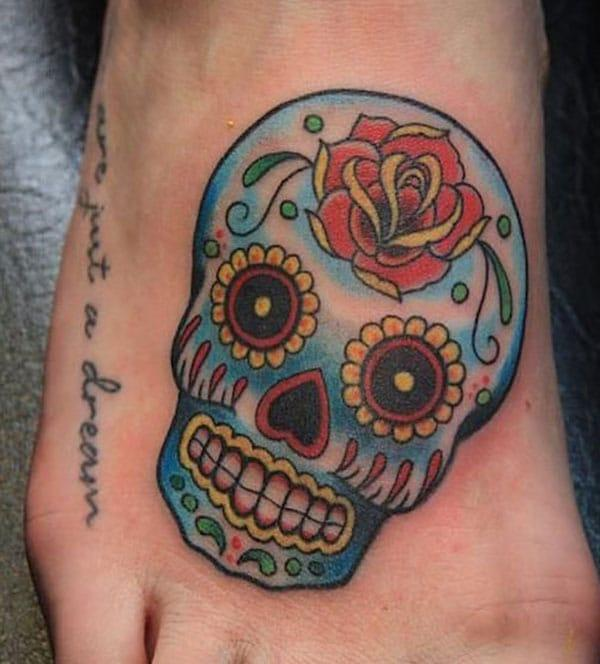 The sugar skull tattoo with rose on feet of female