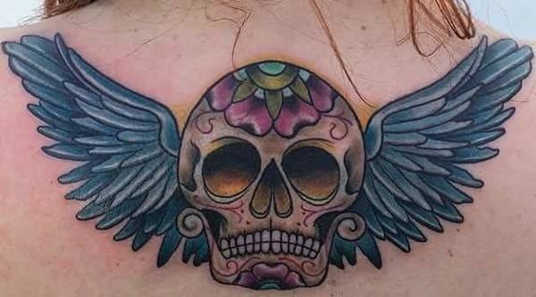 महिला की पीठ के शीर्ष पर पंखों के साथ सबसे अच्छा चीनी खोपड़ी टैटू