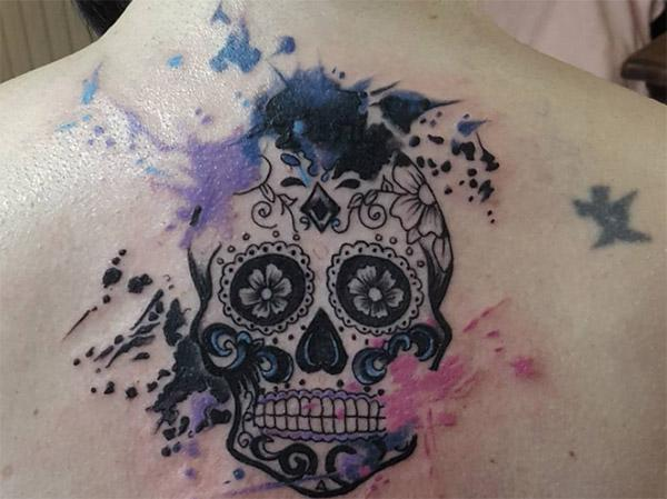 The touchy and real sugar skull tattoo on female top of the back.