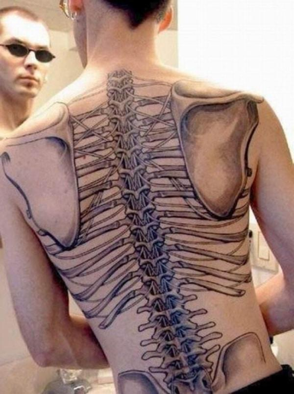 Spine tattoo on the back with a rib cage design makes a man look heroic and stately