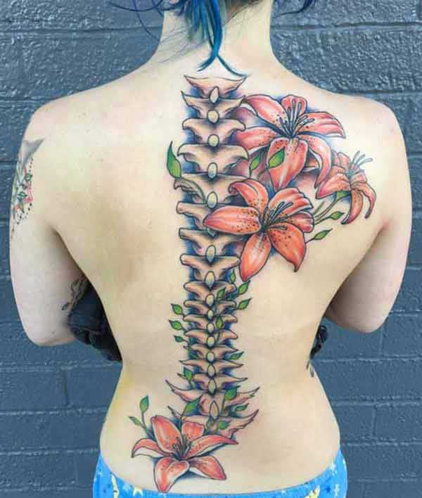 Spine tattoo on the back with a flower ink design makes a girl look captivating
