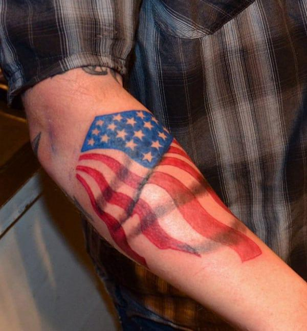 American Flag Tattoo on the back lower arm gives men ostentatious look