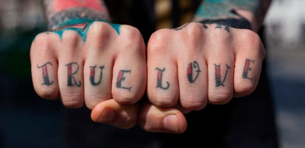 Knuckle Tattoo with a pink and black ink design, writing make a man look Stunning