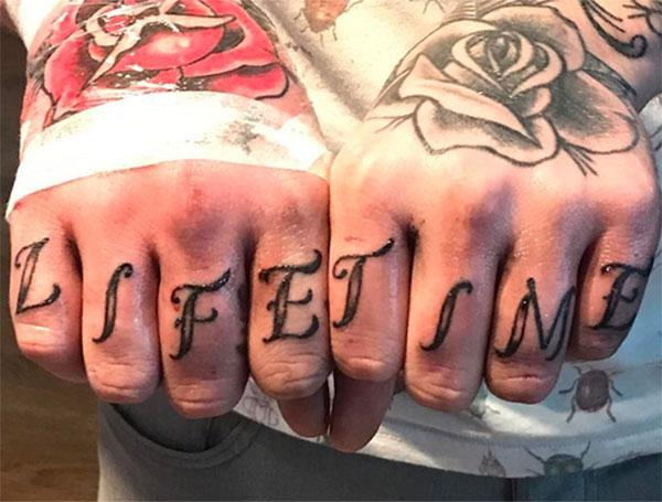 Knuckle Tattoo with a writing having a black ink design makes them look Flashy