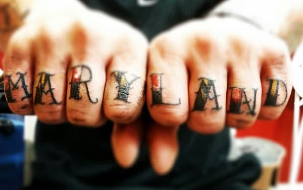 Knuckle Tattoo with a black writing brings the spruce appearance in men