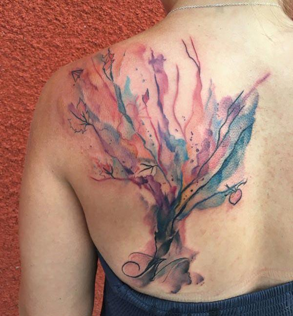 Watercolor tattoo on the back with a flower design brings the elegant and captivating look