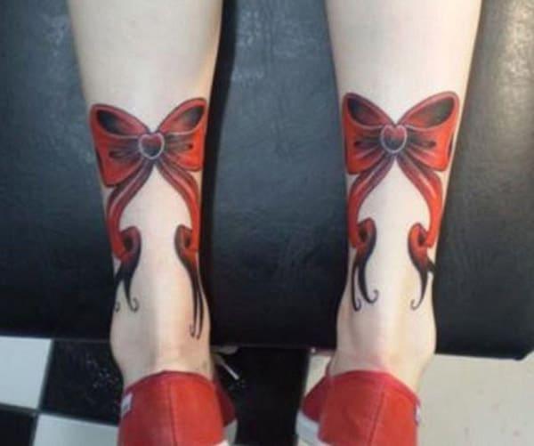 Tatu tunduk dengan dakwat reka bentuk oren di bahagian belakang kaki memberikan pandangan gadis yang menawan.