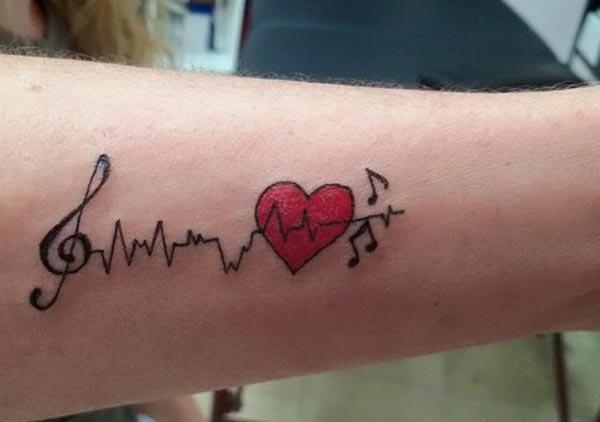 Heartbeat Tattoo with red love ink design on the lower arm make a girl look pretty