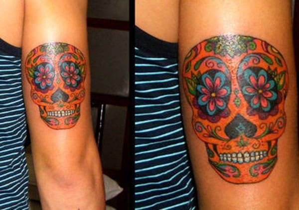 A tatuaxe do cráneo de azucre no dorso do brazo dunha nena