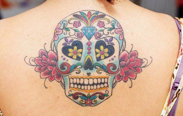 Mellor e curto tatuaje do cranio de azucre no punto traseiro dunha rapaza