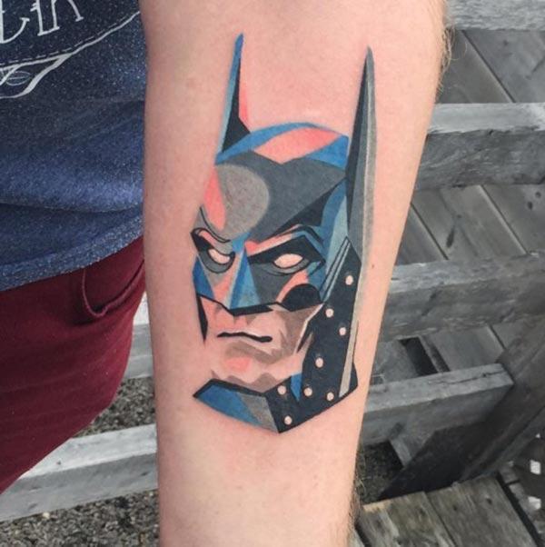 အောက်ပိုင်းလက်မောင်းပေါ် Batman တက်တူးထိုးနေတဲ့လူကိုအောင်မြင်ကျော်ကြားပြီးဆွဲဆောင်မှုရှိတဲ့လူငယ်လေးတွေကိုကြည့်စေသည်