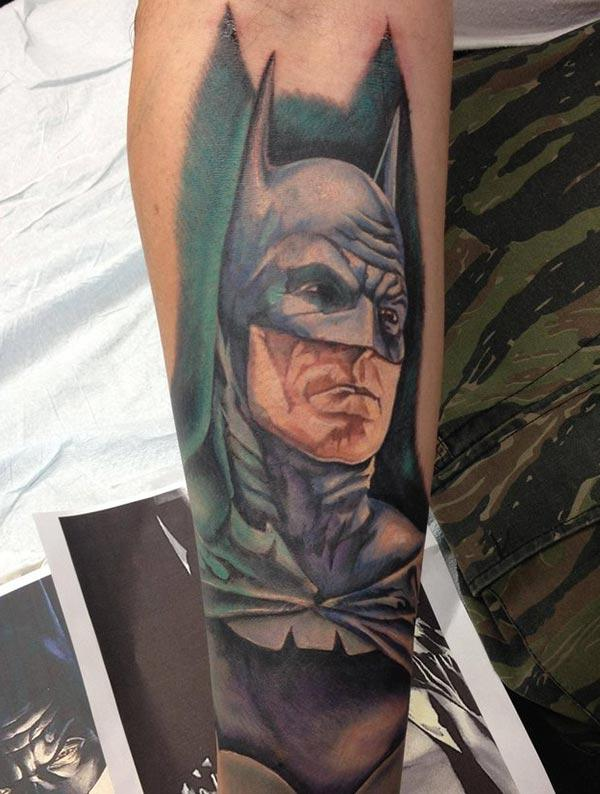 Batman tattoo with a blue ink design on the lower arm shows their foxy look