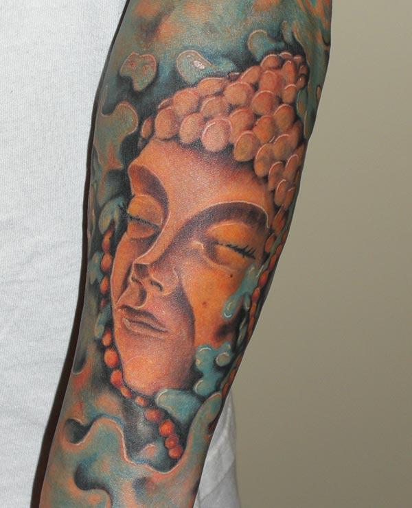 Buddha tattoo with a brown ink design on the lower arm shows their foxy look