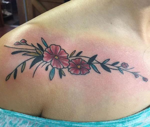 Collar Bone Tattoo with a pink ink design flower brings a feminist look