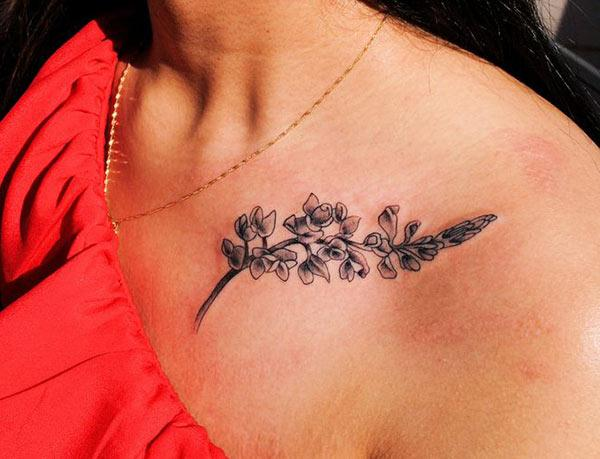 Collar Bone Tattoo with a brown flower ink design makes women look marvelous