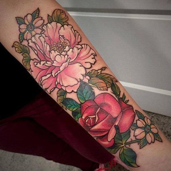Forearm Tattoo with a pink flower make a woman look captivating