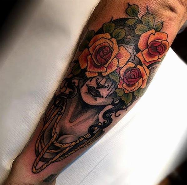 Forearm Tattoo with a face and orange flower ink design make them appear more admirable