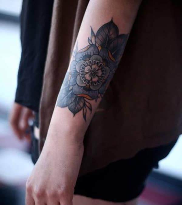 Forearm Tattoo with a green flower ink design brings the appealing look