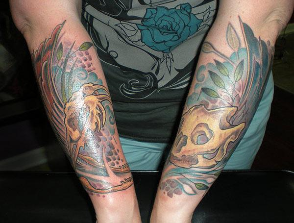 Forearm Tattoo with a skull and blue flower background, ink design make them look cool