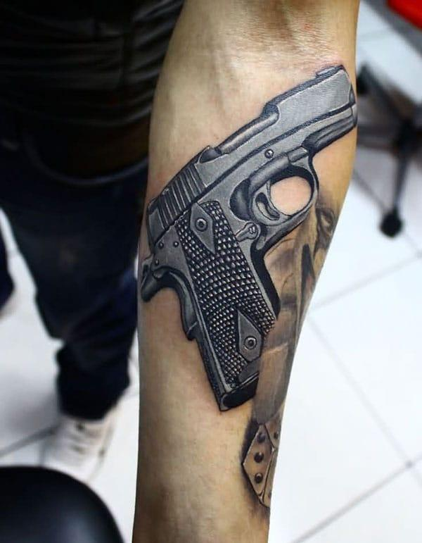 Gun Tattoo on the arm with a black ink design makes a man appear charming