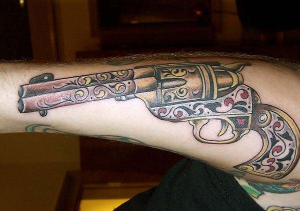 Gun Tattooon the arm makes a man look gallant