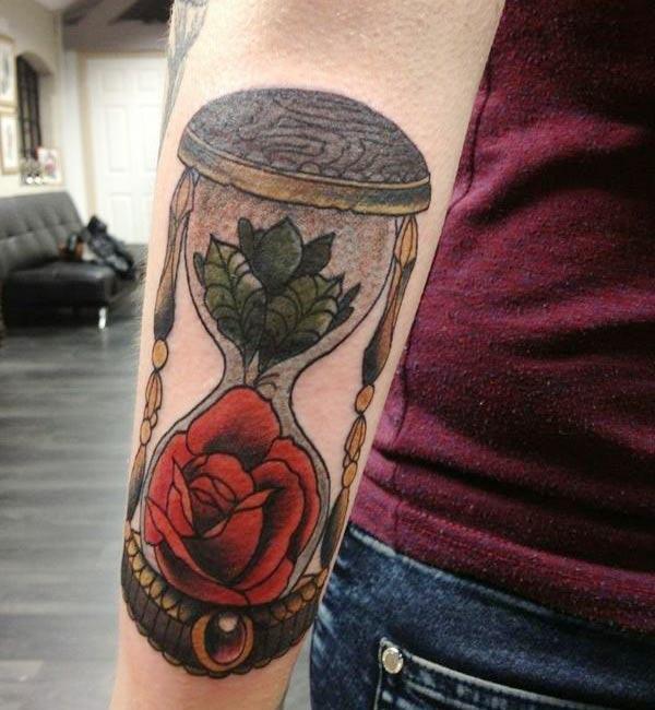 腰の腕の砂時計のタトゥーはピンクのインクデザインで、存在感があります。