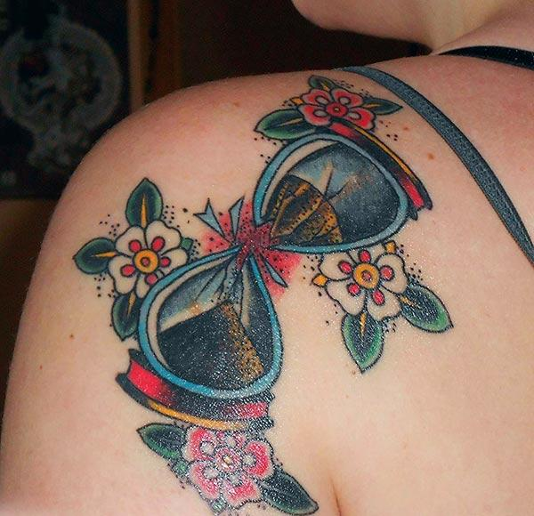 Hourglass tattoo on the back shoulder makes a woman look attractive