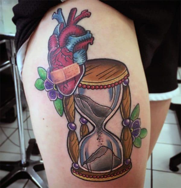 Hourglass tattoo for the thigh brings their feminist look.
