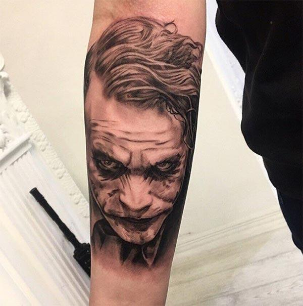 Joker Tattoo with a blue ink design on the lower arm shows their foxy look