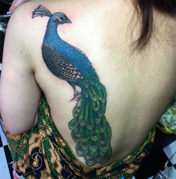 Peacock Tattoo at the back brings the captivating and lovely look