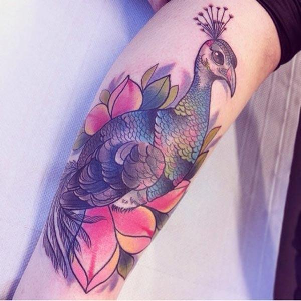 Påfugl tatovering med en blå blekkdesign på underarmen viser deres foxy utseende