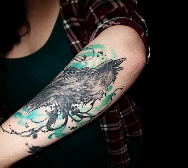 This Raven tattoo design with a colorful ink makes the left arm look fabulous