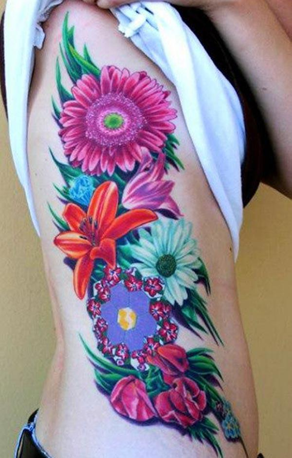 Side tattoo with a pink and purple flower design make a man look foxy
