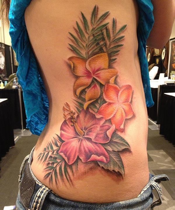 Side tattoo for men with a pink flower ink design brings their artful appearance