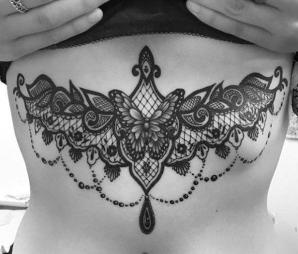 Sternum tattoo for Women with a black ink design make them look radiant