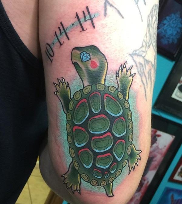 L'omi fannu un tatu di Turtle divinu in u so spallezza ghjusta per facenu attraente