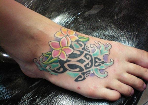 Turtle tattoo for Women with a pink and orange ink, flower design make them look lovely.