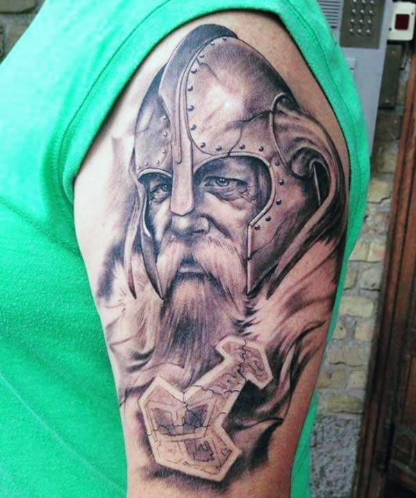 Viking Tattoo am linken upper arm maachen e Mann sech elegant