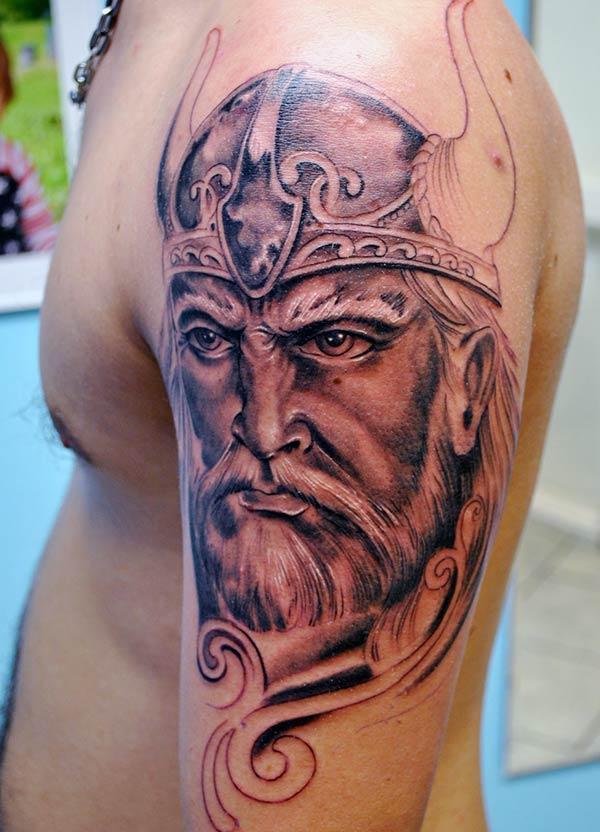 Vikingi tätoveering pruuni tindi kujuga õlale teeb mehe stiilse väljanägemise