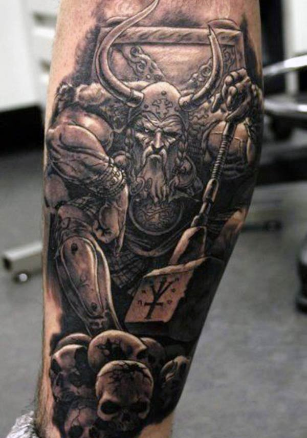 The dark design ink of the Viking tattoo on the foot matches the skin color give a man a dapper look