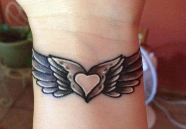Wing tattoo on the wrist makes a woman look captivating