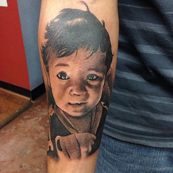 Baby tattoo on a lower arm makes a lady look exquisite