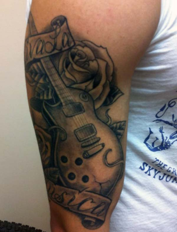 Guitar Tattoo on the right arm make a man have an august look