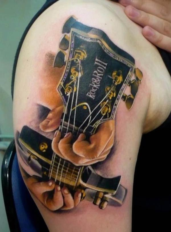 Guitar Tattoo with a black ink design makes a man look elegant