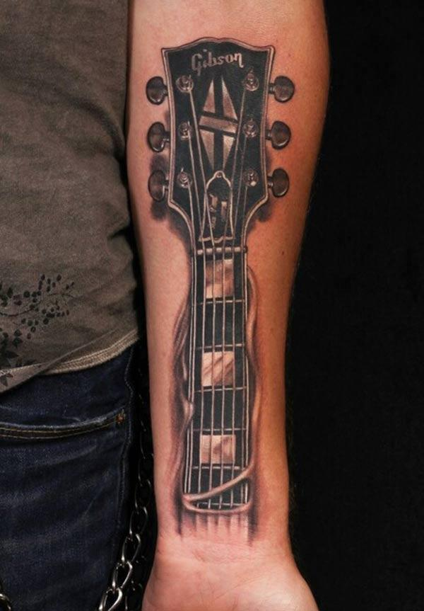 This black ink design of the Guitar Tattoo front lower arm matches the skin color to make a man look admirable
